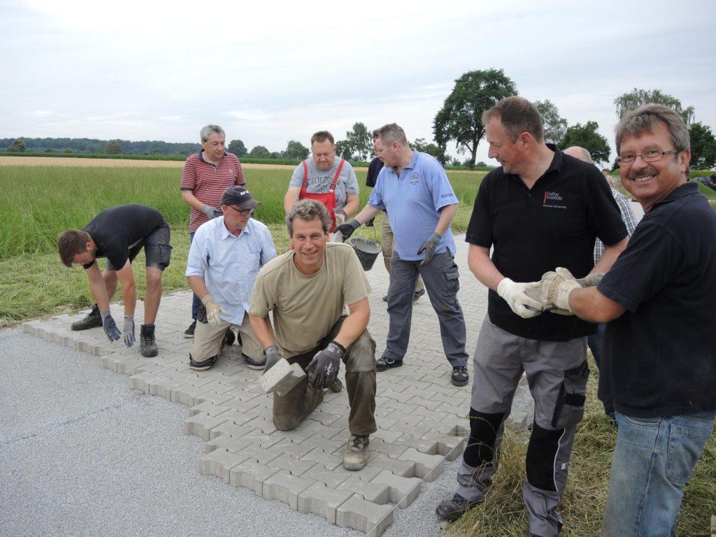 Hand in Hand gehen derzeit die Pflasterarbeiten für den Bau des Kreisschützenfestplatzes in Oberntudorf. Voran gehen Kreisschützenkönig Michael Wessel (vorne knieend Mitte), AK-Infrastruktur-Vorsitzender Henrik Höhl (vorne 2.v.l.) und auch Brudermeister Norbert Ernst (rechts).